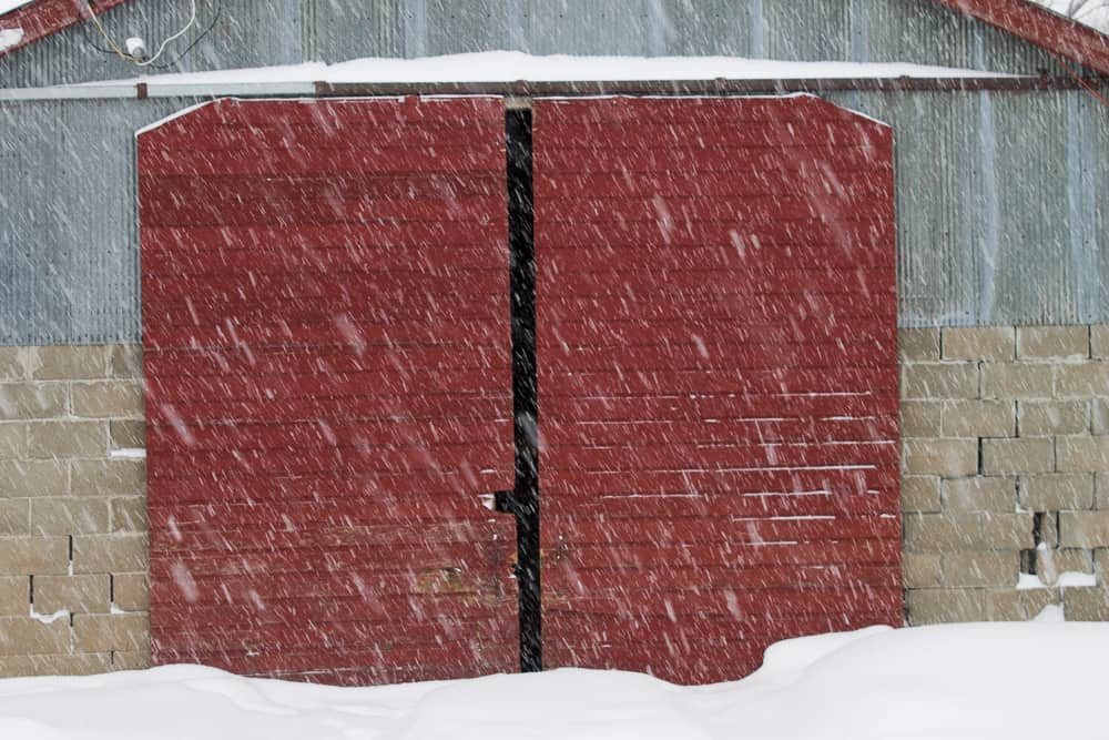 red barn door in snow