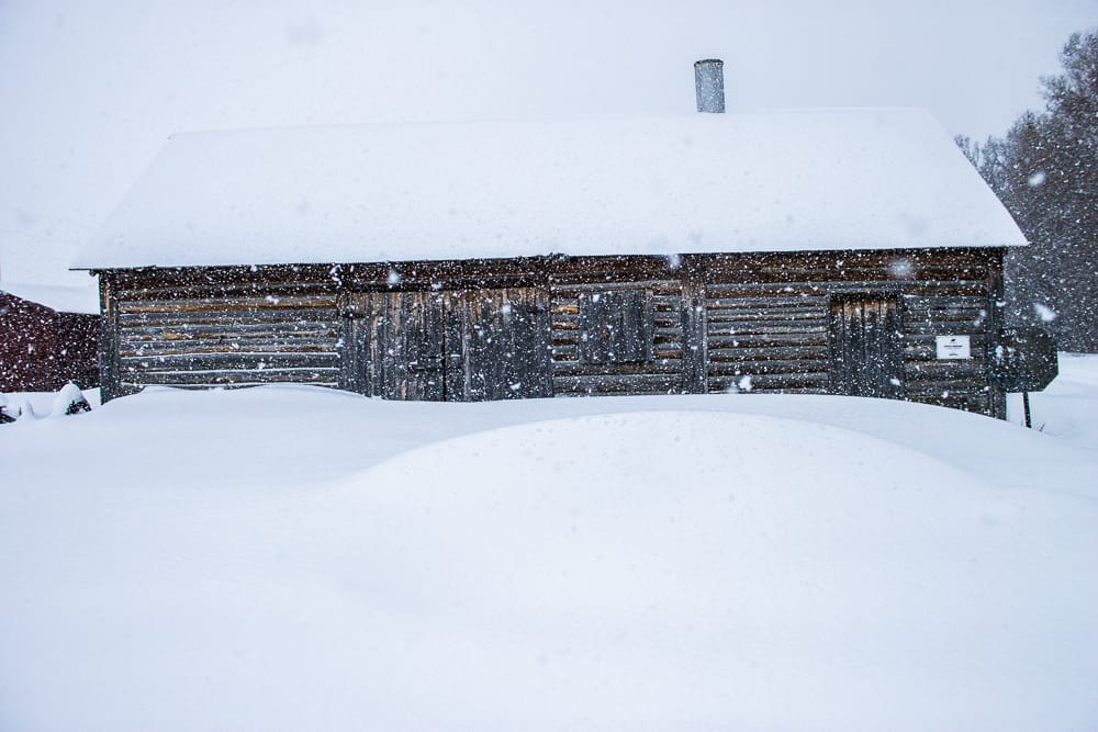 snow covered log barn
