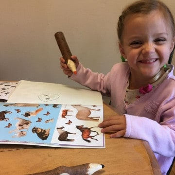 little girl laughing as she colors a picture