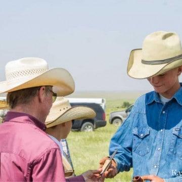 Two cowboys trading pocketknives