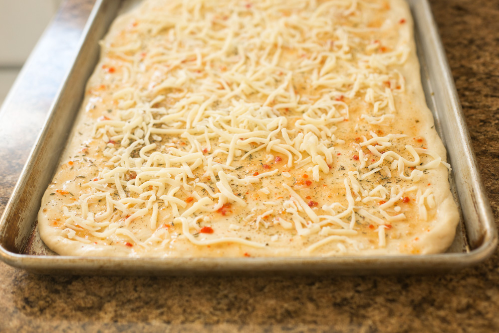 raw dough spread with dressing and sprinkled with cheese