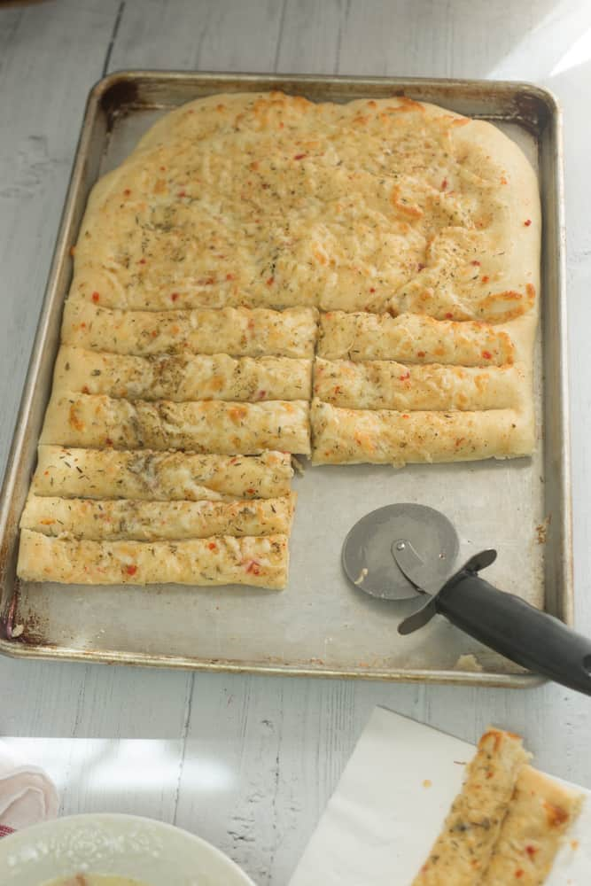 baked and sliced cheesy breadsticks in pan