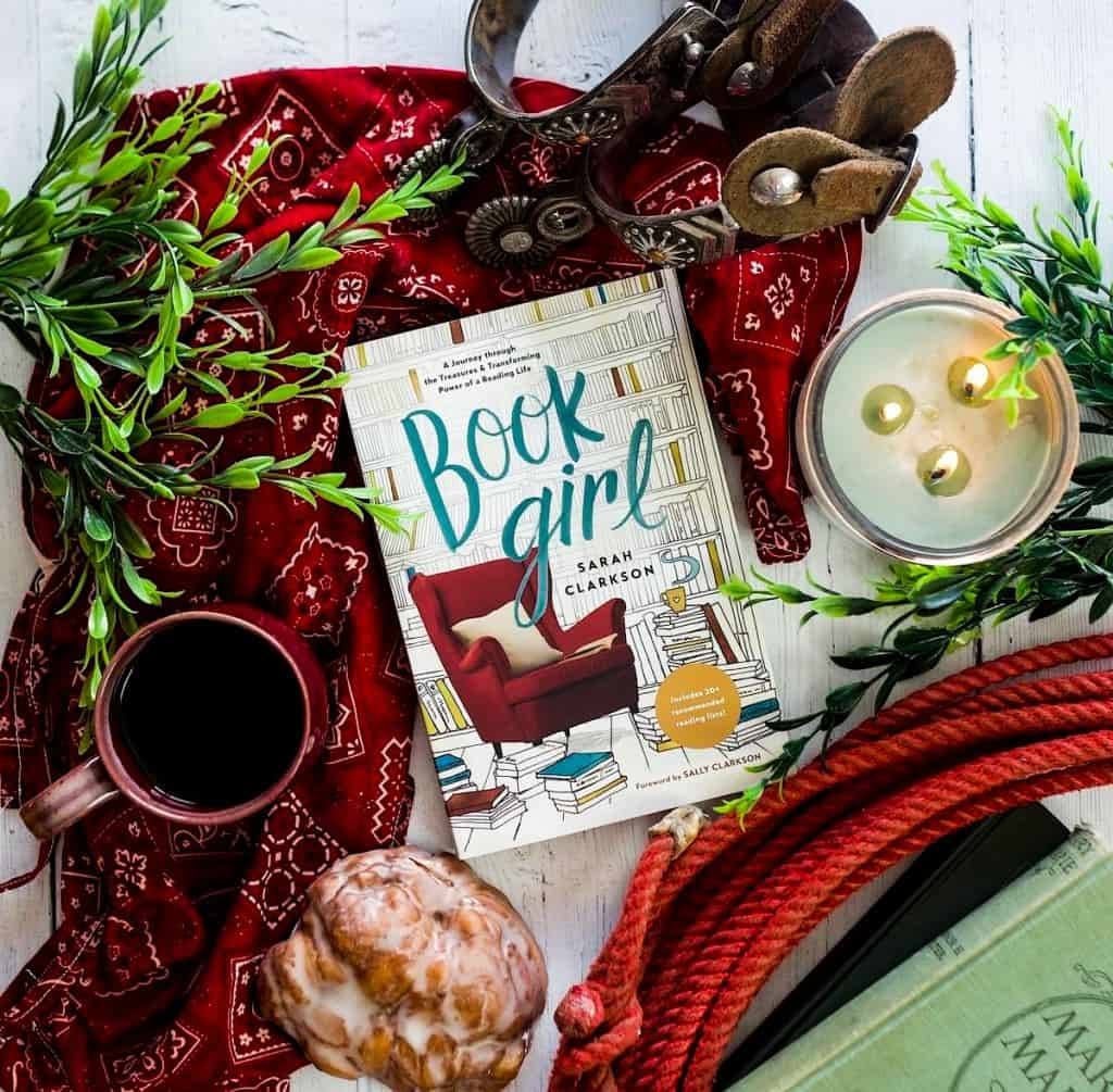 themed book photo, book, mug, candle, and pastry on a cloth