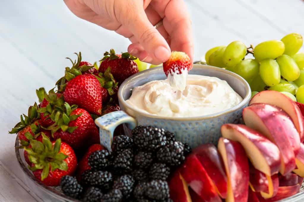 hand holding strawberry dipping into fruit dip