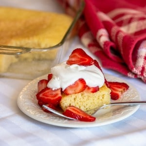 pound cake on a plate, with strawberries and whipped cream on top