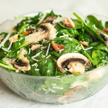 spinach mushroom salad in glass bowl