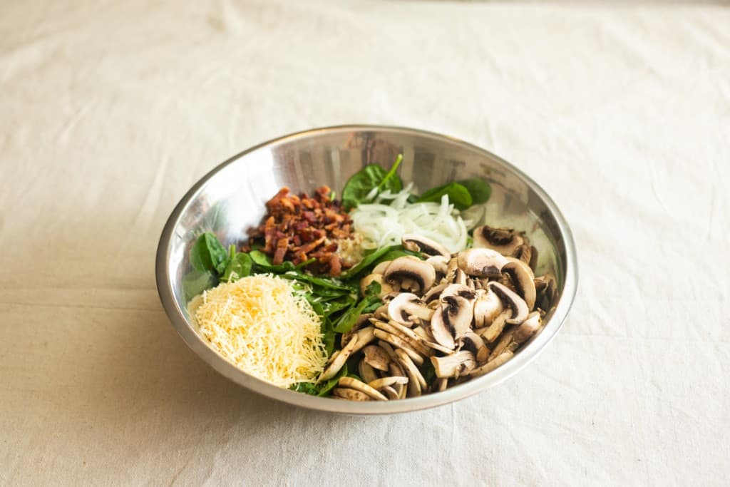 spinach, mushrooms, onions, parmesan cheese and bacon in salad bowl