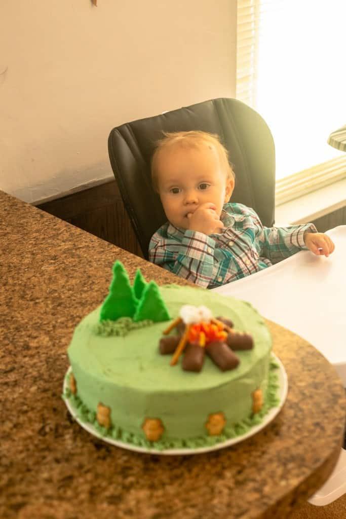 camping birthday cake next to small boy