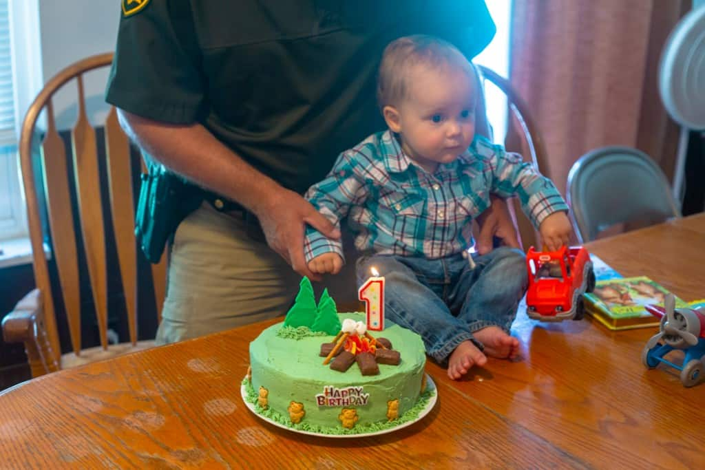 camping birthday cake beside small boy