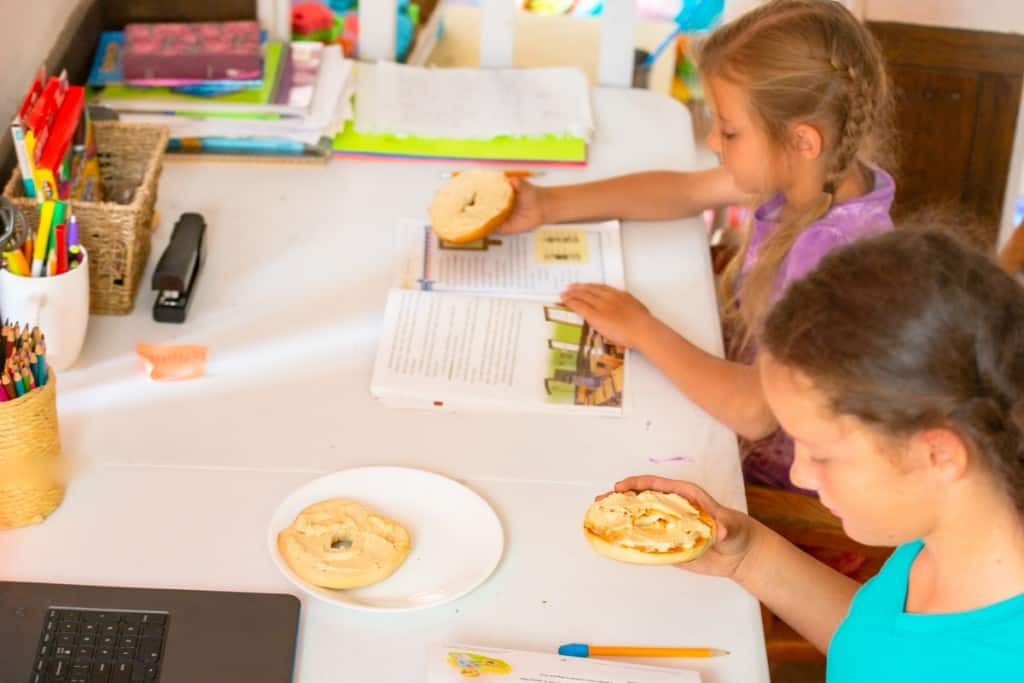 kids eating bagels while doing schoolwork