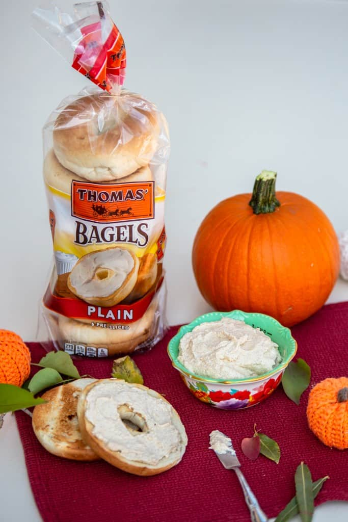 Pumpkin Spice cream cheese on table with bagels and pumpkin