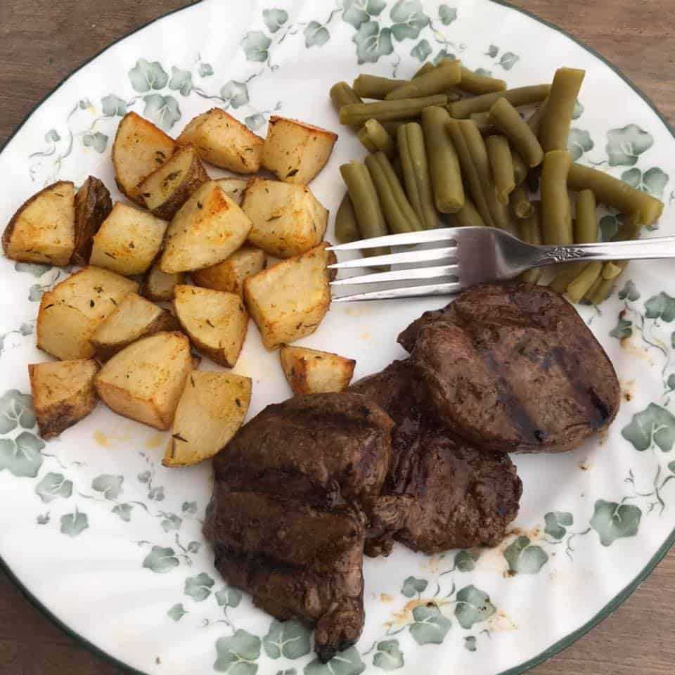 dinner plate with venison steak, potatoes, and green beans