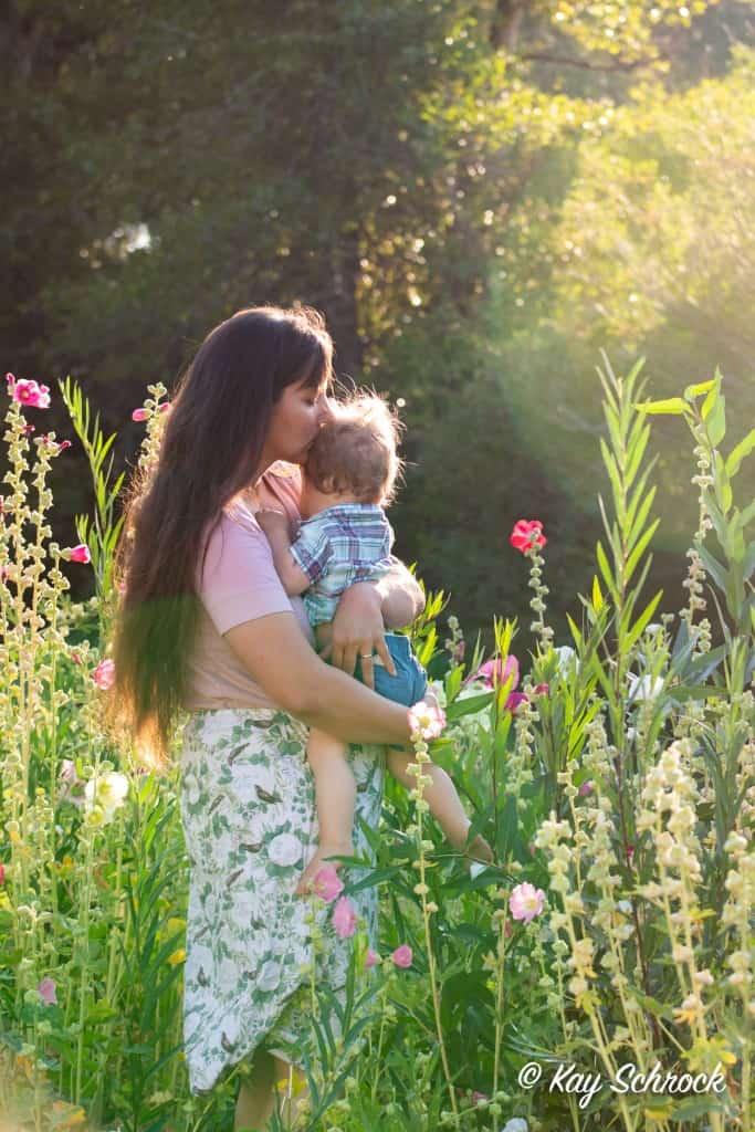 mom holding toddler in flower garden