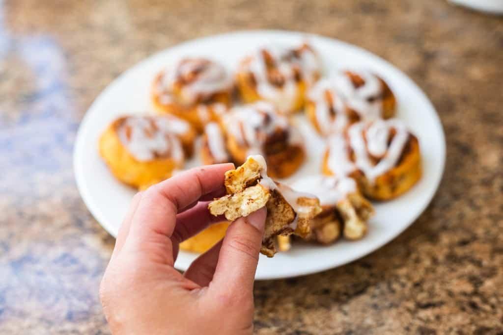 hand holding half of an air-fried cinnamon roll