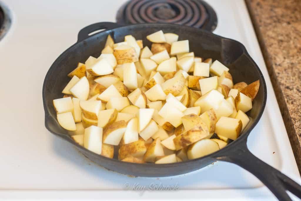 raw potatoes in skillet