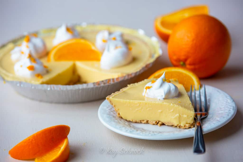 orange mousse pie sliced on plate surrounded with oranges