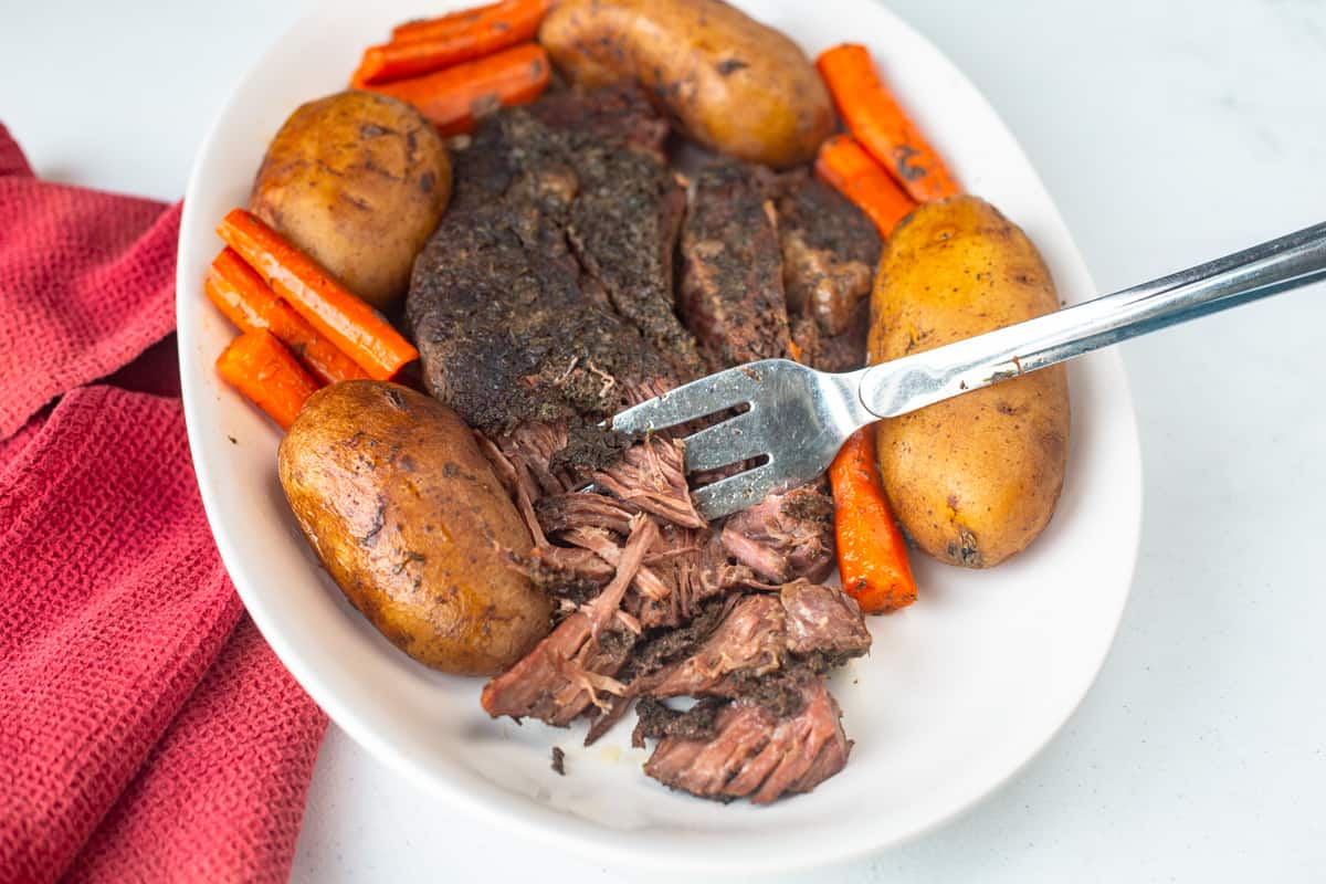 beef pot roast and vegetables on white platter