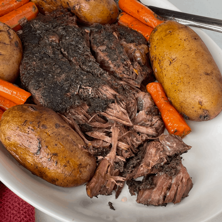 Crockpot Beef Roast on platter with potatoes and carrots
