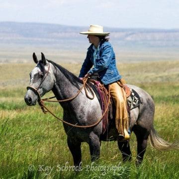 cowgirl sitting on horse in teh prairie
