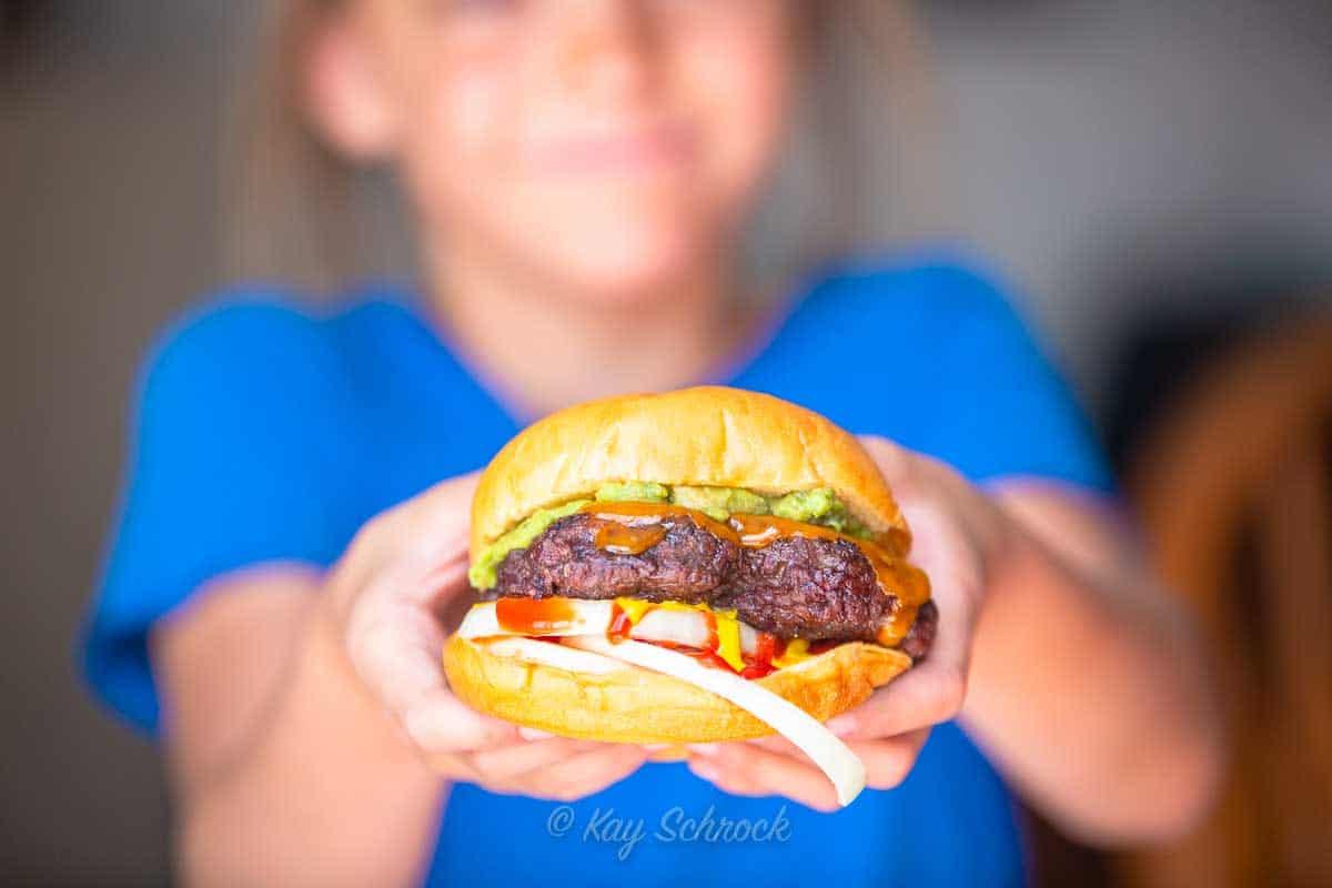 girl holding thick elk burger