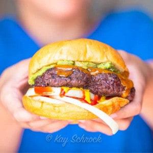 elk burger in bun with toppings