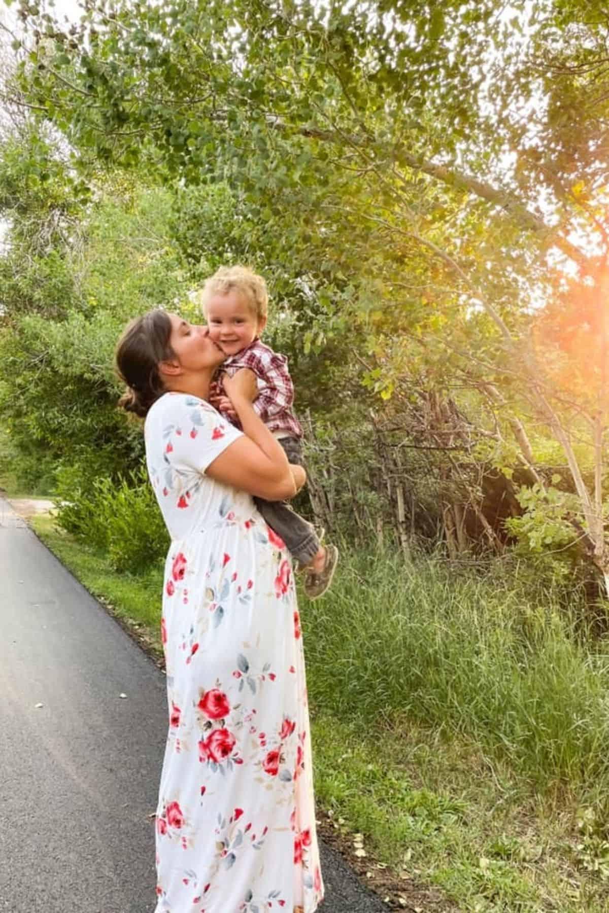 mom in dress kissing toddler