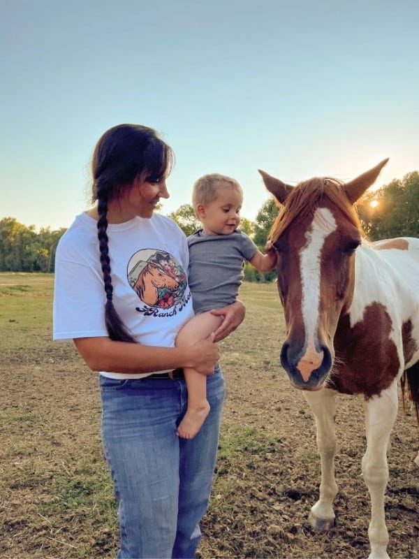 mom holding toddler who is petting a horse