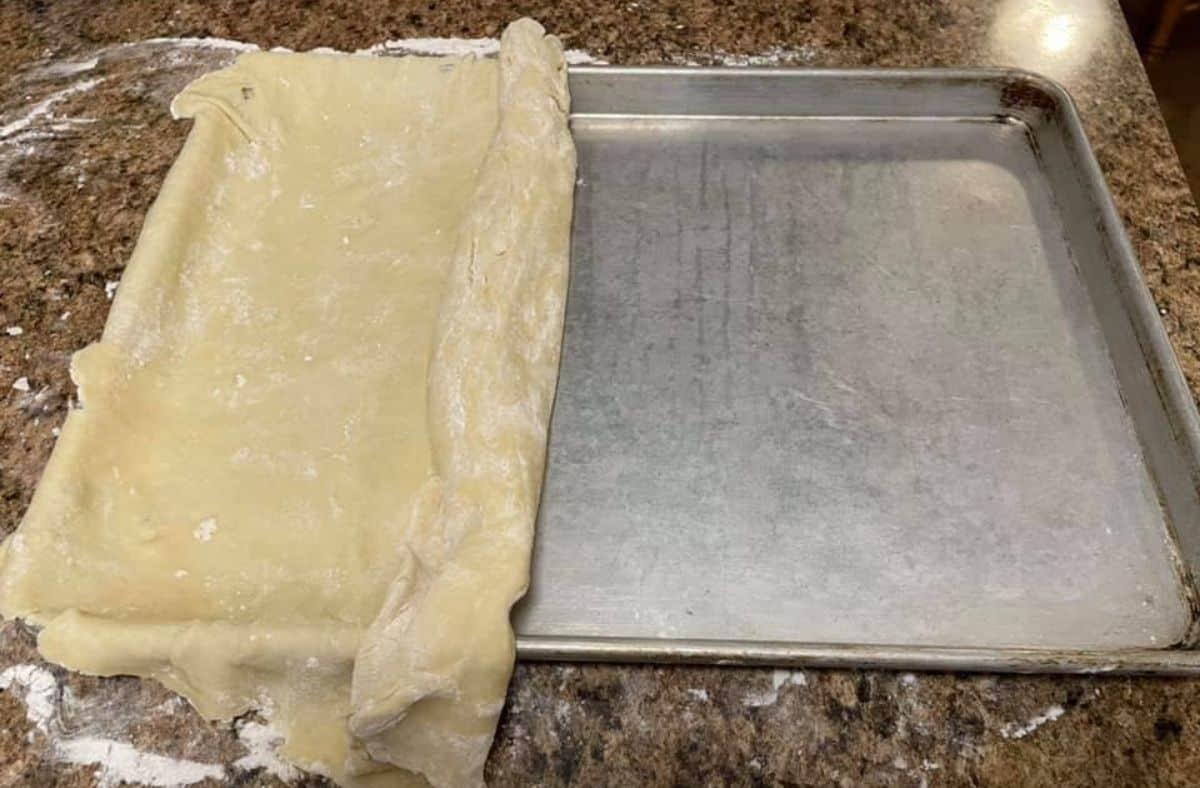 pie crust for slab pie half unrolled in pan